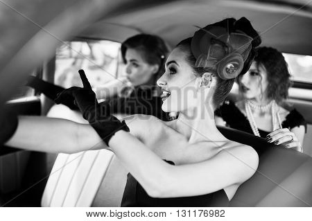 Three Young Girl In Retro Style Dress Seat On Old Classic Vintage Car And Having Fun Emotions