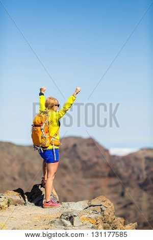 Woman successful hiking climbing silhouette in mountains motivation and inspiration landscape on island and ocean. Female hiker with arms up outstretched looking at view on La Palma Spain.