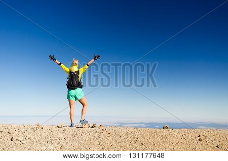 Woman successful hiking climbing silhouette in mountains motivation and inspiration landscape on island and ocean. Female hiker with arms up outstretched on mountain top looking at beautiful view on Tenerfie Spain.