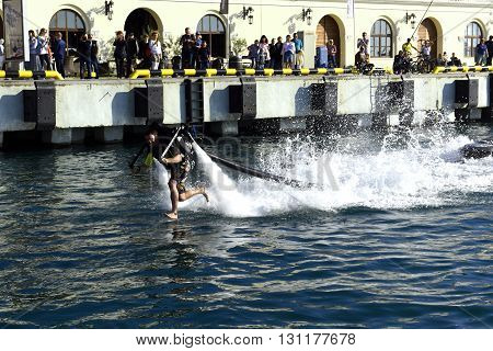 Sochi, Russia, on 2 may 2016. Open, free show of yachts and boats. The performance of the man on a water jet pack. A man runs through water.