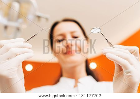 Female dentist using probe and mouth mirror on an dental exam. Patient's view.
