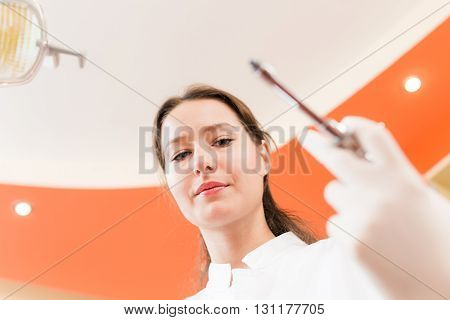 Serious female dentist holding a syringe in hand . Patient's view. Focus on the woman