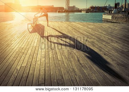 Woman exercising on the bridge under sunlight.