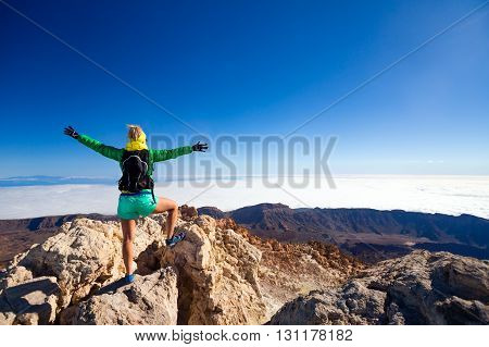 Woman successful hiking climbing in mountains motivation and inspirational landscape on island and ocean. Hiker with arms up outstretched on mountain top looking at beautiful view on Tenerfie Spain.
