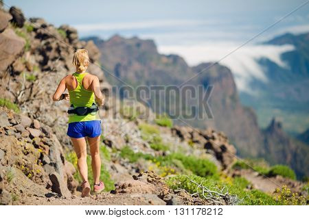Young woman running in mountains on sunny summer day. Beauty female runner jogging and exercising outdoors in inspirational landscape rocky trail footpath on La Palma Canary Islands.