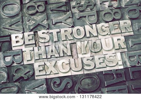 be stronger than your excuses phrase made from metallic letterpress blocks with dark letters background