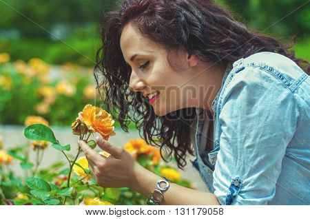 Pretty young woman in the park with a flower.