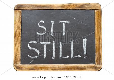 sit still exclamation handwritten on vintage school slate board isolated on white