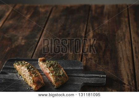 Slightly unfocused two raw pieces of salmon in white wine sause with spices and herbs presented on stone deck prepared for grill Healthy nutrition meal isolated on side of rustic wooden table