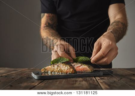 Man Cooks Healthy Meal On Rustic Table, Decorate With Mint Leaf Two Raw Pieces Of Salmon In White Wi