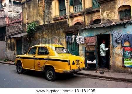 KOLKATA, INDIA - JANUARY 20, 2013: Vintage yellow taxi car stopped at the old street on January 20, 2013 in Kolkata India. Kolkata has a density of 814.80 vehicles per km road length.