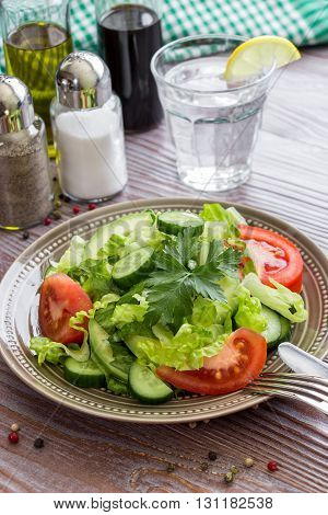 In foreground a salad of lettuce, tomato, cucumber, avocado, near cutlery, pepper peas and on wood background a glass of water, salt, pepper, balsamic, olive oil. Fresh salad for lunch. Vertical.
