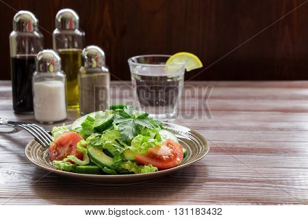 Left a salad of lettuce, tomato, cucumber, avocado in dark wood background a glass of water, salt, pepper, balsamic, olive oil, right empty spase for text. Healthy fresh salad for lunch. Horizontal.