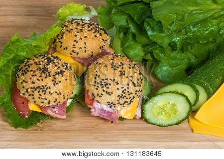 three hamburgers  with vegetables and bacon on the wooden desk