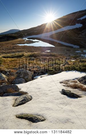 Sunrise over the mountains. Spring landscape with a lake. Last snow on the slopes. Carpathians, Ukraine, Europe
