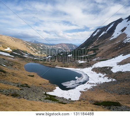 Mountain Lake. Spring landscape. Overcast day with clouds. Carpathians, Ukraine, Europe