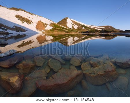Mountain Lake. Stones in the water at the bottom of the lake. Spring landscape with last snow on the slopes. Sunny morning. Carpathians, Ukraine, Europe