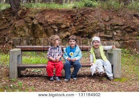 Children sitting on the bench laughing and having fun outdoors in the park. Friendship happiness excitement. happy childhood concept.
