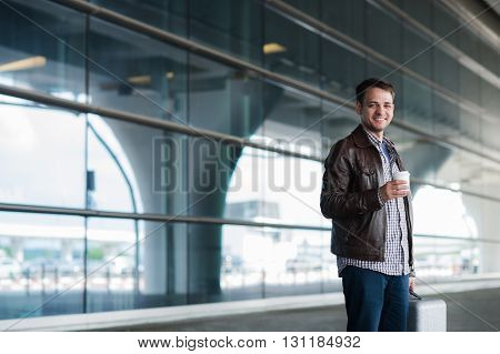 View of a Young attractive man drinking coffee on his way