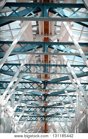 Glass ceiling footbridge with metal structures and circular lamps. Vintage tinted.
