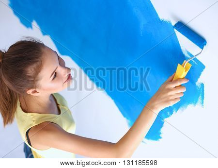 Happy beautiful young woman doing wall painting, standing on ladder