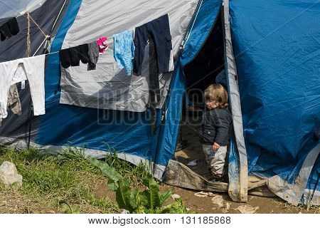 IDOMENI, GREECE - MARCH 17, 2015: A little girl stands by her tent on March 17 2015 in the refugee camp of Idomeni Greece. For several weeks more than 10.000 refugees and immigrants wait here for the borders to open.