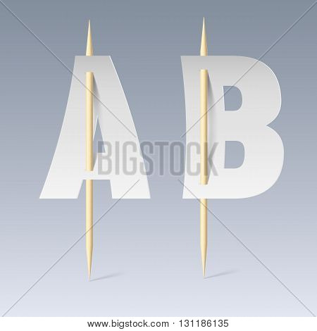 White paper cut font on toothpicks on grey background. A and B letters