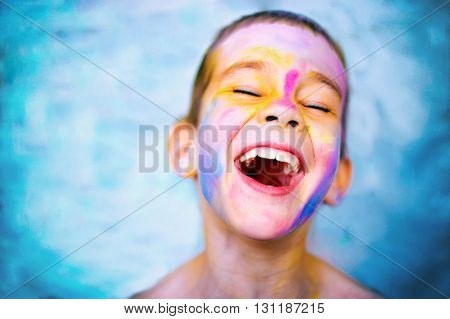 laughing kid with paint stained face. boy laughs cheerfully enjoying active games and creativity. head thrown back, eyes closed. copy space for your text