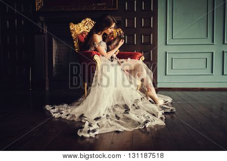 Beautiful young woman with cat sitting in a trendy dress