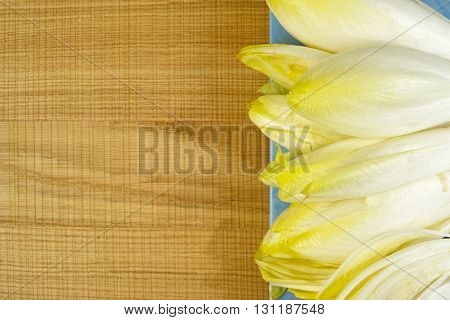 Fresh Chicory Salad leaves placed on a blue plate on wooden background copy space