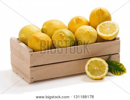 Wooden crate with fresh lemons isolated on white background.