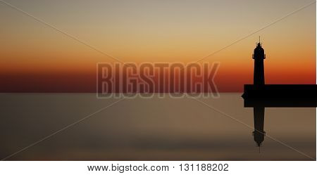 Lighthouse silhouette on the background the evening calm sea