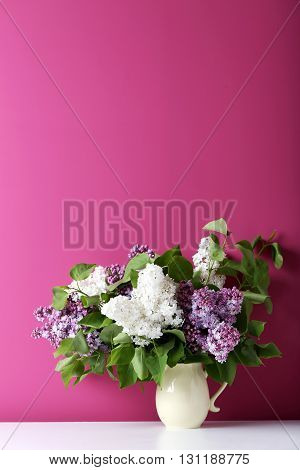 Blooming lilac flowers in the basket on pink background