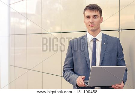 Smiling businessman with his laptop next to the office building
