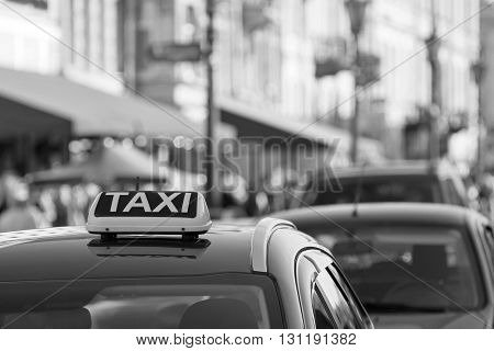 symbol or sign with an inscription of a taxi is located on a car roof on an indistinct background city of monochrome color