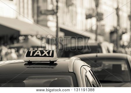 symbol or sign with an inscription of a taxi is located on a car roof on an indistinct background city of sepia color