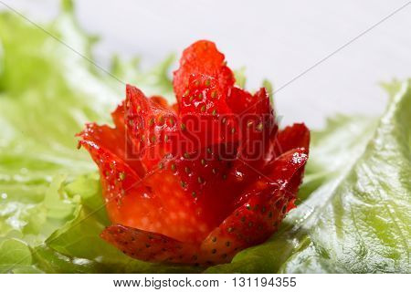 Red flower from strawberry on fresh greens. Close up small depth of sharpness