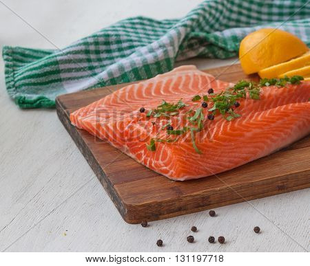 Fillet of red fish and lemon on a cutting board next to the jars with spices