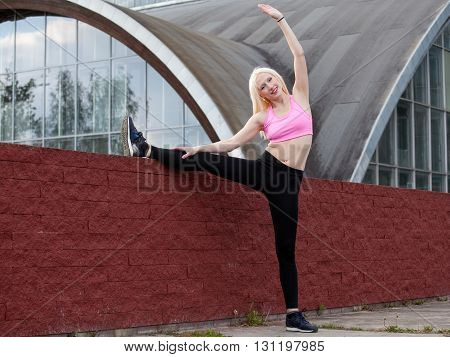 Street workout. Young blonde woman is doing leg stretching outdoors warming up before training performing a tilt to the leg