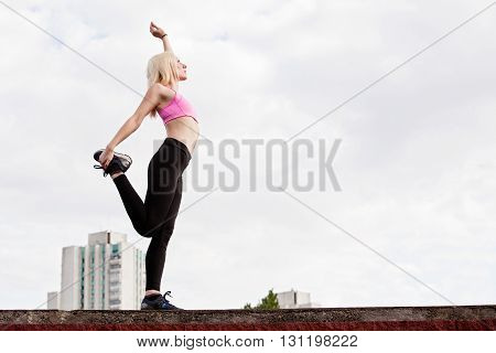 Young blonde woman is doing leg stretching outdoors warming up before training pulling the hip on a background of clouds