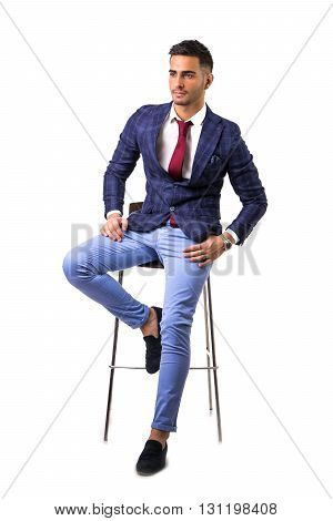 Handsome young man in blue business jacket and jeans posing isolated on white background in studio, sitting on stool. Full body shot