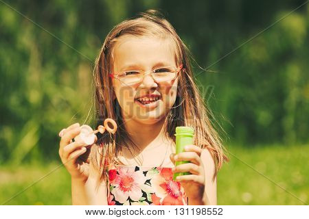 Smiling little girl child blowing soap bubbles outdoor. Joyful kid having fun in park. Happy and carefree childhood. Instagram filtered.
