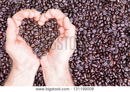 Hands holding coffee beans in shape of heart while placed against surface spread with many more