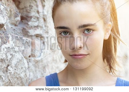 portrait of a beautiful teenager girl leaning against a wall