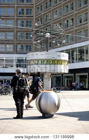 BERLIN, GERMANY - MAY 10: Passersby stroll in good weather all around the world clock on the Alexander Place in Berlin on May 10, 2015 in Berlin.