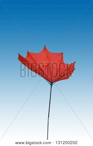 By wind folded and isolated red parasol.