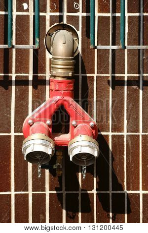 The close-up of a fire hydrant with water connections on a tiled wall.