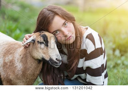 woman is stroking a brown sheep at a meadow