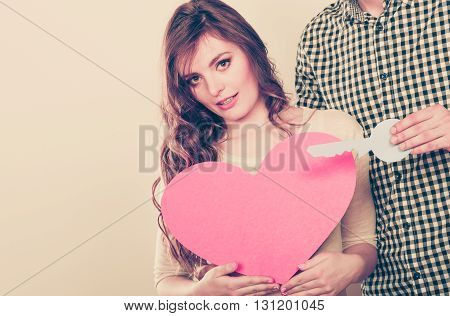 Smiling young couple holding paper key to unlock heart sign love symbol. Loving husband and wife. Instagram filtered.