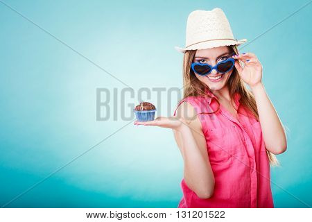sweet food happiness and people concept. Smiling summer fashionable woman wearing straw hat heart shaped sunglasses holds cake cupcake in hand blue background